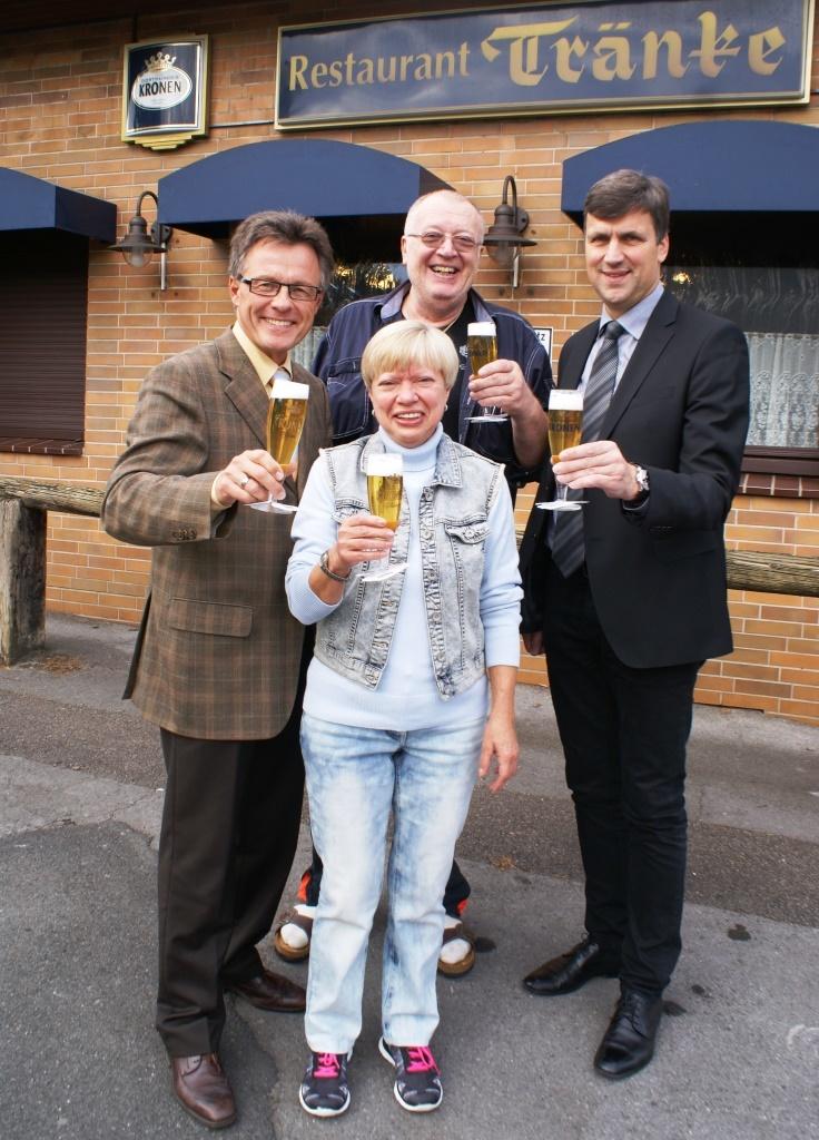 """Alexander Olschowka (li.) und Thomas Schneider (re.) von den Dortmunder Brauereien stoßen mit Wirtepaar Rolf und Annegret Oehme auf die 50-jährige Gastronomietradition in der """"Tränke"""" an."""